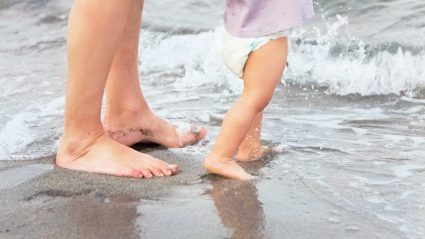 Adult and toddler feet paddling in the shallow water at the family friendly beach
