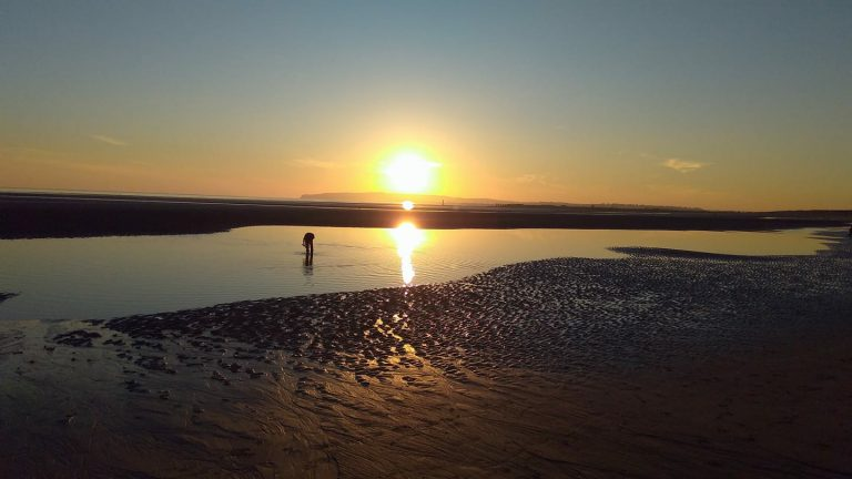A boy paddles in a shallow lagoon at Camber Sands beach at sunset.
