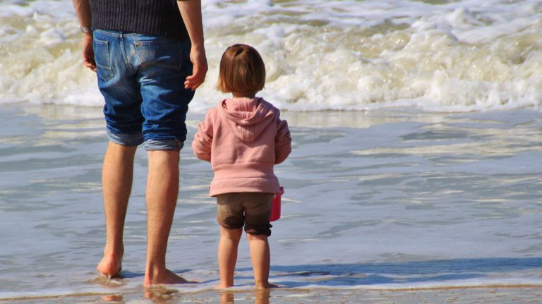 A man and a small child paddle in the sea