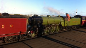 A green steam engine at Dungeness RH&D Railway station