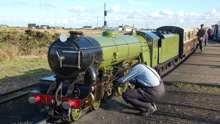 A green steam engine on the Romney Hythe and Dymchurch Railway at Dungeness Station