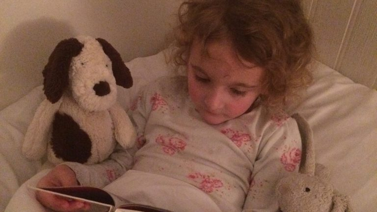 A child reads in bed to Daisy Dog and Bunny at our family friendly holiday cottage, Camber Sands