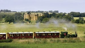 View of Kent and East Sussex Railway with Bodiam Castle in the distance, 1066 Country