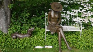 A bronze statue of a sausage dog with lady on a bench at Pashley Manor Gardens, Ticehurst