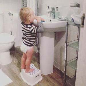 Toddler staring at bathroom basin